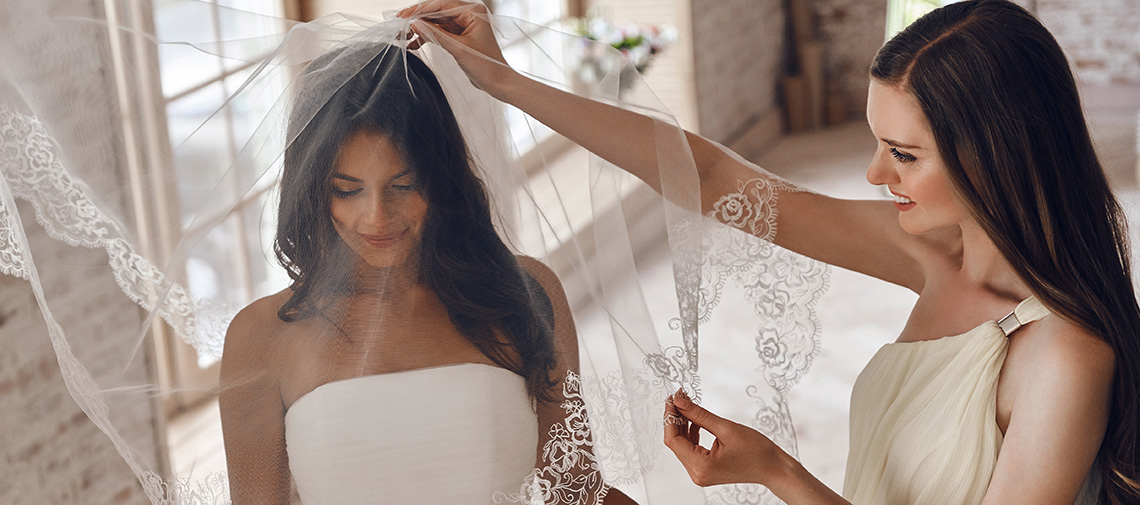 Sensual bride. Bridesmaids helping bride to put on a veil and sm